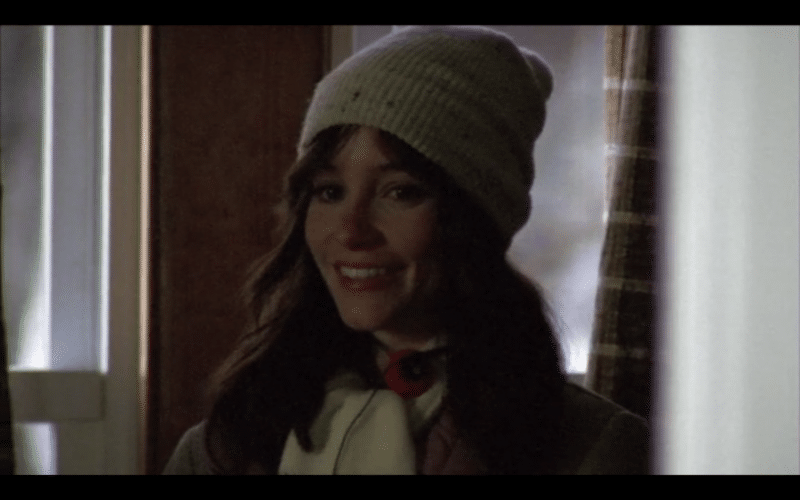 A smiling girl in a winter hat, inside a dimly-lit room.