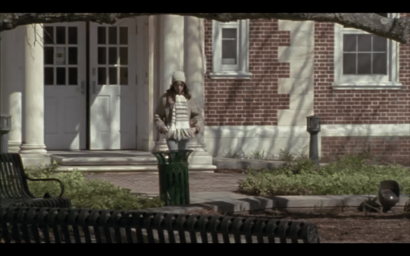 A medium-long shot of a girl walking out of a school dormitory in the fall.