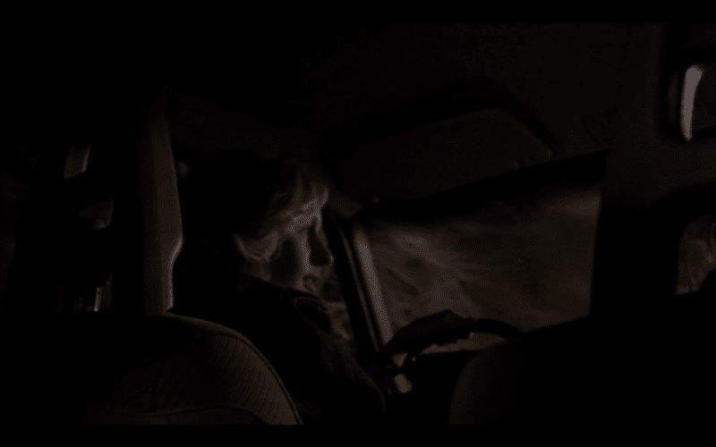 A girl in a car. Dark woods outside. We are looking up at her from the backseat.
