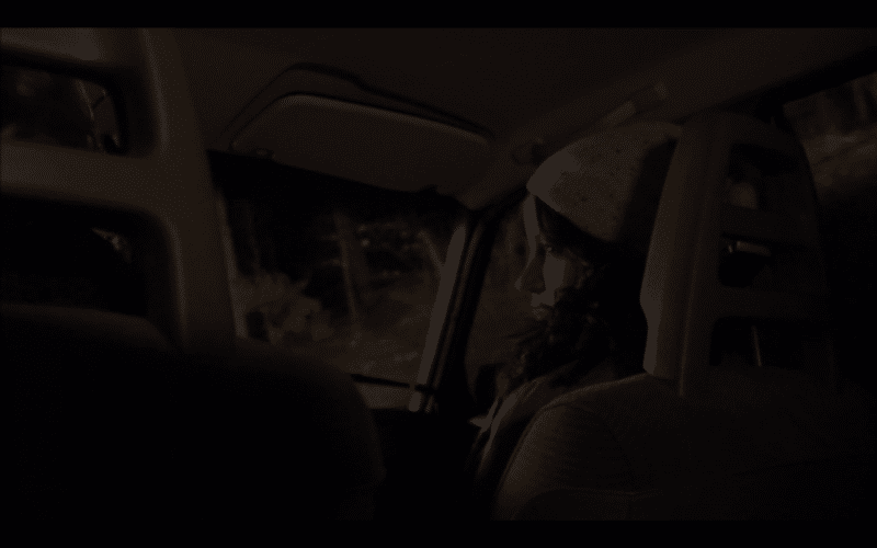 Another girl in a car. We're looking up at her from the backseat.