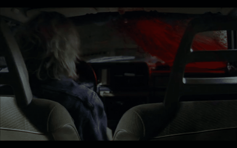 Blood all over the windshield of a car. We're looking at it from the backseat.