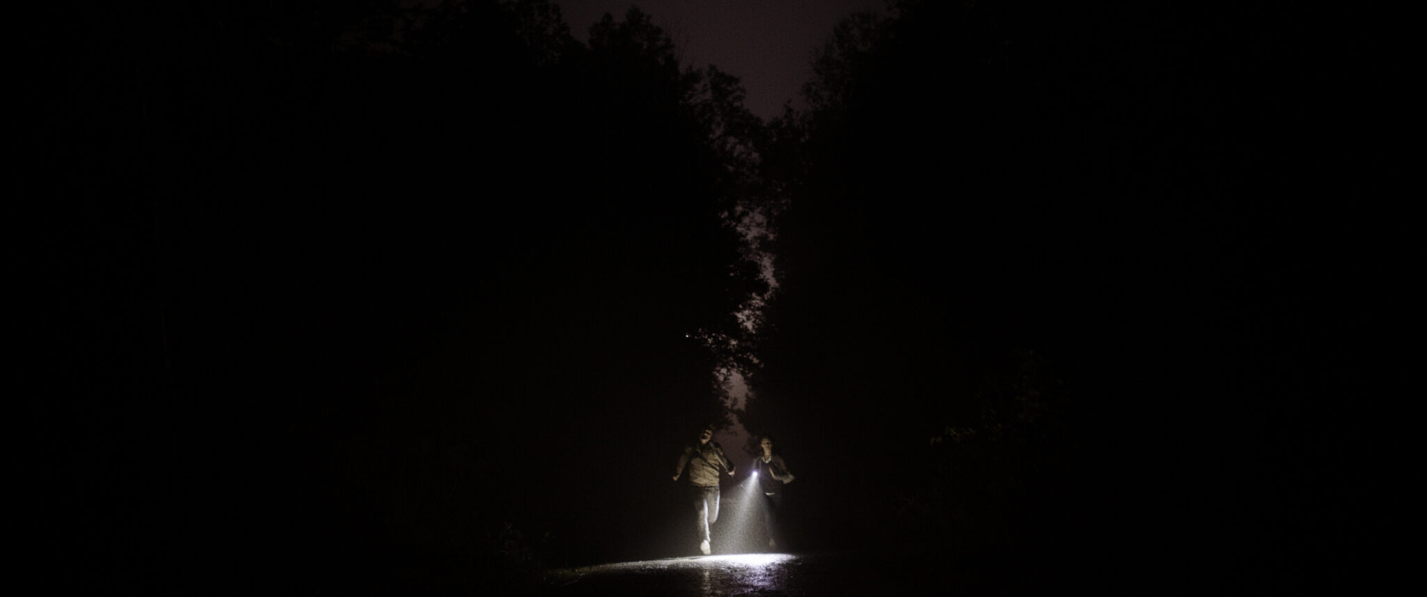 A still from The Toll, featuring Cami and Spencer running in pitch darkness